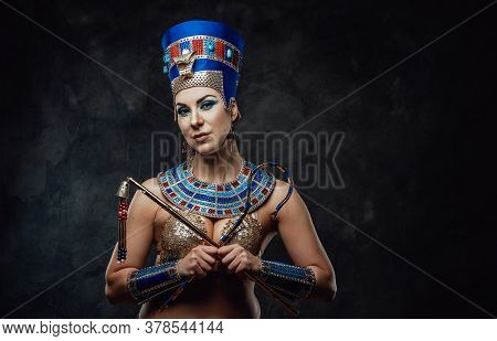 Lady In Traditional Egyptian Blue And Gold Costume With Distinctive Symbols Of Power In Her Hands