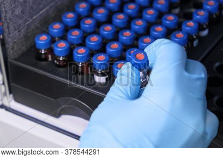 Close Up Woman Hand In A Rubber Gloves Put Sample In A Glass Vial With Blue Cap Into The Autosampler