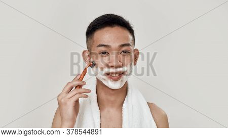 Shave Easily. Portrait Of Shirtless Young Asian Man With Towel Around His Neck Shaving His Face, Loo