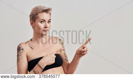 Portrait Of Half Naked Tattooed Woman With Short Hair Looking At Camera Pointing Index Fingers At Th