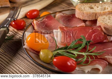 Thinly Sliced German Black Forest Ham With Sliced Ciabatta Bread, Tomato And Olives.