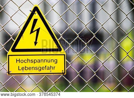 Warning Symbol For High Voltage Danger To Life. Yellow Triangular Warning Sign In German On Fence Of