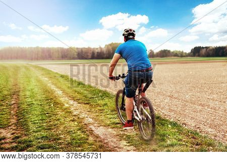 Cyclists Cycling, Cycling. In The Park With Grass In The Background And Forest. Sunlight Whit Shine.