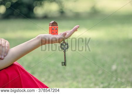 Small House In A Beautiful Female Hand, Vintage Key, The Concept Of Buying Your Own Home, Real Estat