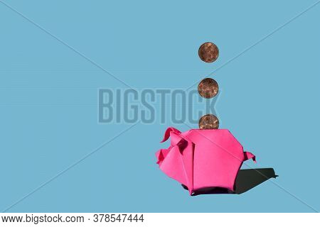 Pink Origami Piggy Bank And Three One Cent Coins On Blue Background, Hard Shadows.