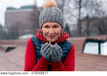 Beautiful Mature Woman Drinking Hot Tea From Thermos In Park And Relaxing After Active Fitness Train