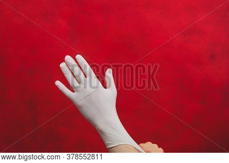 Hand In Medical Glove On A Red Background. Person Puts On Surgical Gloves On A Red Background