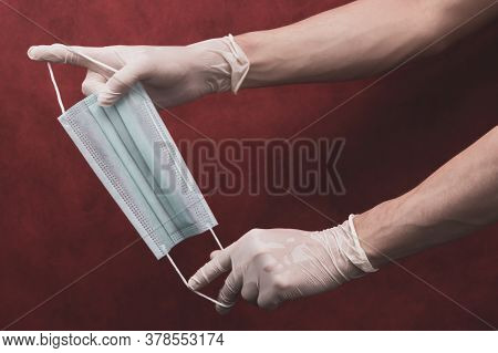 Hands In Protective Gloves Stretch A Medical Mask On A Red Background. Preventive Measures Against R