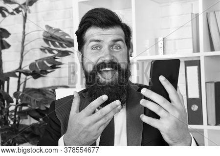 Got Happy News. Happy Professional Hold Mobile Phone. Bearded Man With Happy Look In Office. Success