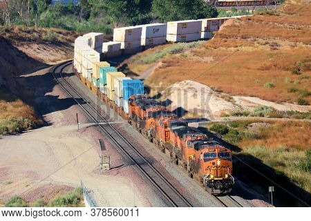 July 27, 2020 In Cajon Pass, Ca:  Freight Train With Four Locomotives Hauling Uphill Rail Cars Uphil