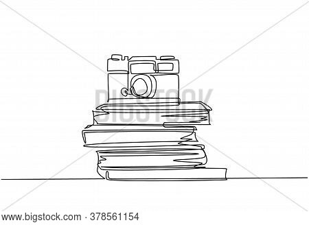 Single Continuous Line Drawing Of Vintage Classic Analog Pocket Camera Above Stack Of Books On Desk.