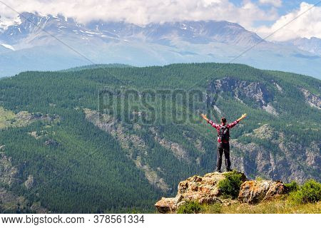 Man Traveling With Backpack Hiking In Mountains.  Man Arms Outstretched By The Nature Enjoying Freed
