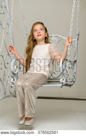 Beautiful Little Girl Swinging In The Studio On A Swing. Concept Of A Happy Childhood, Family Well-b