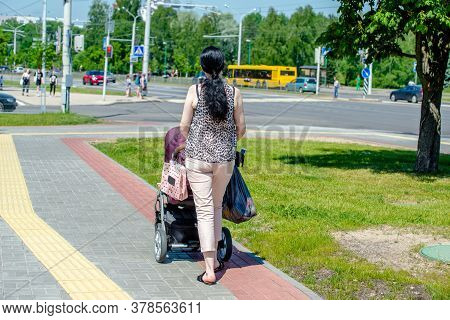 Mother Wheeling A Pram In The City Street