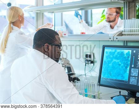 Scientist and students working in lab. Doctor teaching interns to make blood analyzing research. Coronavirus, chemistry, bacteriology, virology and health care