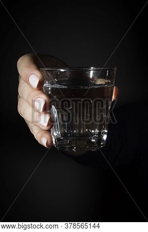 Hand With A Glass Of Water On A Black Background