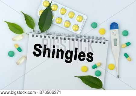 On The Table Are Pills, A Thermometer, Leaves And A Notebook With The Inscription -shingles. The Con
