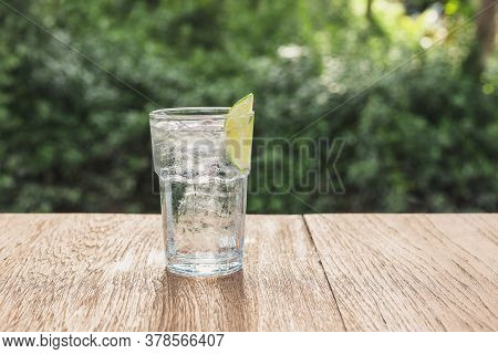 Glass Of Fresh Drinking Water And Slice Of Lime On Wooden Table.