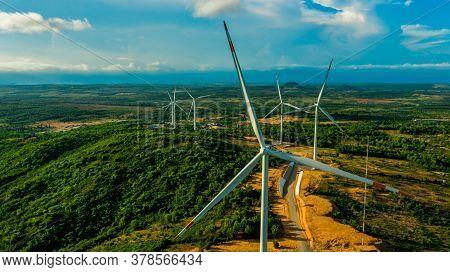 Wind Turbines Or Wind Power Generators At Sunset. Alternative Green Ecological Power Energy Generati