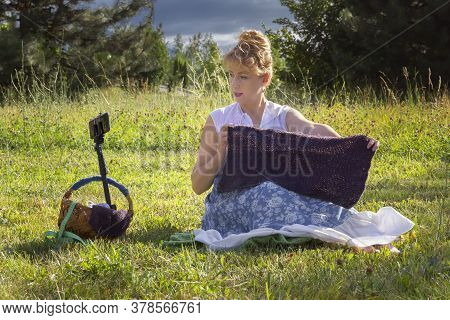 Woman Sits On The Grass In A Park Knitting Wool Clothes On A Knitting Needle And Shows A Knitted Ite