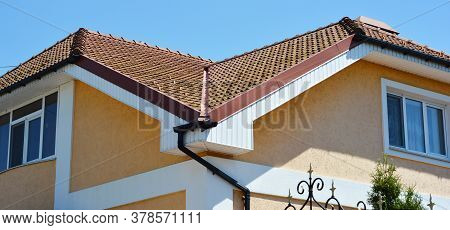 A Close-up On A Red Clay Tiled Roof Valley, Fascia And Rain Gutter System With A Downspout Of A Pain