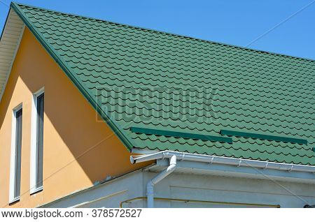 Broken Roof Gutter.  A Close-up On Metal Tiled Gable Roof With Snow Stoppers, Broken Rain Gutter Sys