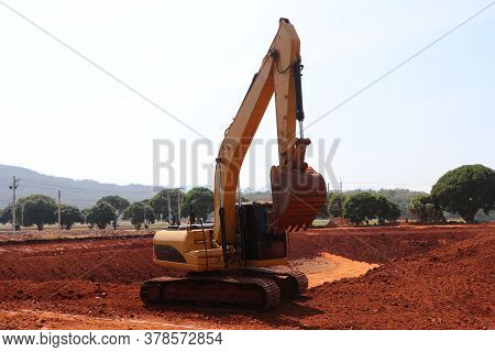 Yellow Alloy Excavator Truck Car Vehicles On The Lateritic Soil Which Is The Area For Digging.