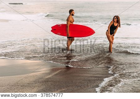 Beautiful Couple Have Fun At The Sea. Couple In Love On The Beach With A Surfboard At Sunset. Beauti