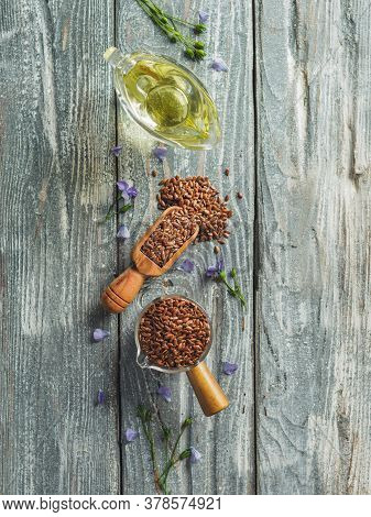 Flax Seeds And Flax Oil. Brown Linen Seeds And Flaxseed Oil On Old Gray Wooden Background. Copy Spac