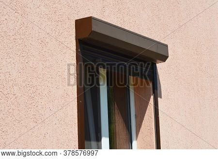 A Close-up On An Open Brown Exterior Pvc Motorized Window Roller Shutter On A Painted House.