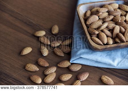Almonds In Small Wooden Bowl. Almonds Laid Freely On Dark Table. Row Of Bowls With Almond Nuts, Top