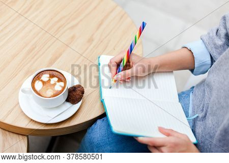 Young Woman Writing Morning Pages With Rainbow Pencil In Paper Notebook At Home. Girl Sitting At Woo
