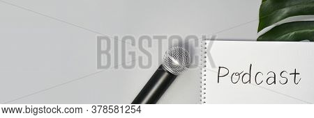 Podcast Concept. White Notebook With Blank Sheet. Black Microphone And Green Monstera Leaf. Audioboo