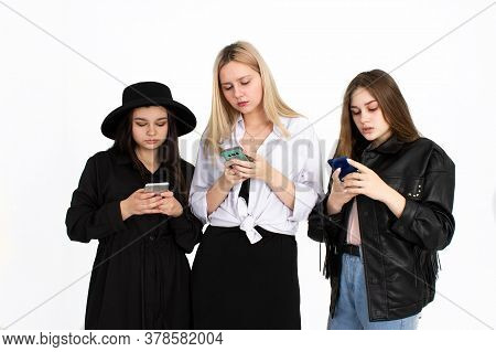 Three Young Beautiful Girls Are Looking At Their Smartphones. Photo On A White Background