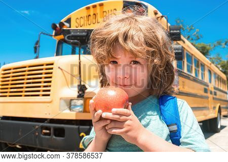 School Boy At The Front Of The School Bus Eating Apple. Child From Elementary School With Bag On Sch