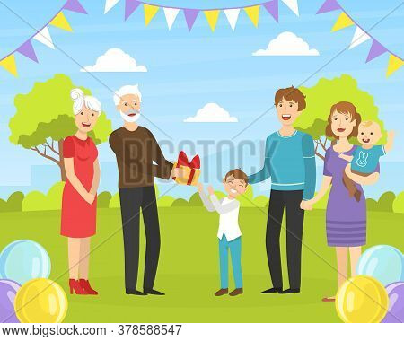 Boy Giving Holiday Present To Happy Grandfather, Relatives Congratulating Grandparent With Birthday