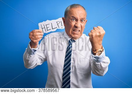 Senior handsome businessman holding paper help message over isolated blue background annoyed and frustrated shouting with anger, crazy and yelling with raised hand, anger concept