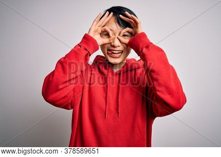 Young beautiful asian woman wearing casual sweatshirt with hoodie over white background doing ok gesture like binoculars sticking tongue out, eyes looking through fingers. Crazy expression.