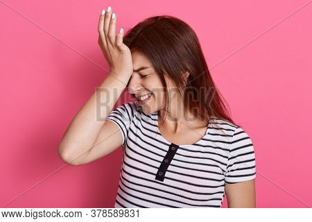 Disappointed Woman Keeps Palm On Forehead, Regrets Did Something Wrong, Dressed Striped T Shirt, Pos