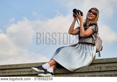 Attractive Beautiful Young Girl Holding Modern Mirror Camera On The Steps Of Stair. Female Traveller
