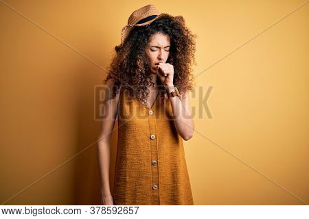 Beautiful brunette woman on vacation with curly hair and piercing wearing hat and dress feeling unwell and coughing as symptom for cold or bronchitis. Health care concept.