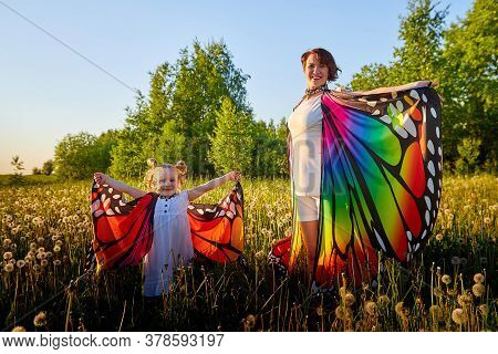 Mother And Daughter With Bright Fabric Like Butterfly Wings Play, Fly, Run, Jump In Meadow Or Field