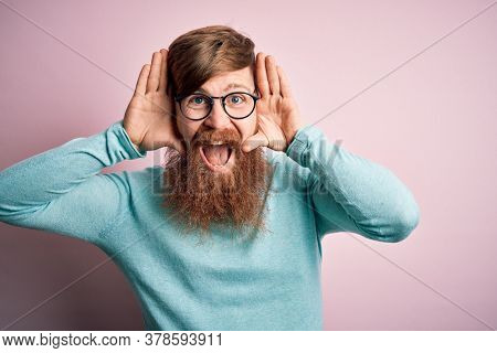Handsome Irish redhead man with beard wearing glasses over pink isolated background Smiling cheerful playing peek a boo with hands showing face. Surprised and exited