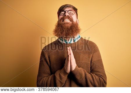 Handsome Irish redhead man with beard wearing glasses and winter sweater over yellow background begging and praying with hands together with hope expression on face very emotional and worried. Begging