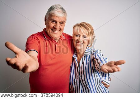 Senior beautiful couple standing together over isolated white background looking at the camera smiling with open arms for hug. Cheerful expression embracing happiness.