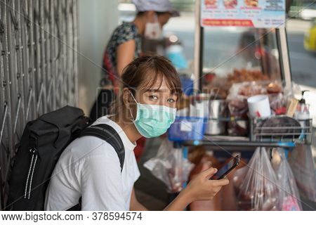Asian Woman With Surgical Face Mask, Carrying Backpack,  Traveling To The City Waiting For Street Fo