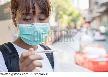 Asian Woman With Surgical Face Mask Feel Tired In Front Of The Road Looking At Thermometer For Check