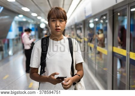 Asian Woman Look Feel Tired Use Smartphon Standing Waiting For Subway, Skytrain, Carrying Backpack,