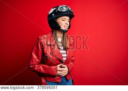 Young beautiful brunette motocyclist woman wearing motorcycle helmet and red jacket with hand on stomach because nausea, painful disease feeling unwell. Ache concept.
