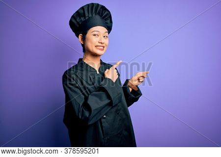 Young beautiful chinese chef woman wearing cooker uniform and hat over purple background Pointing aside worried and nervous with both hands, concerned and surprised expression